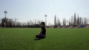 Молодая женщина Active подходящая хорошая смотря сидя на траве огромного стадиона зеленой размышляя штилев наслаждающся теплым со видеоматериал