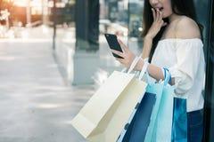 Молодая женщина aisin используя ее whi smartphone и хозяйственной сумки владением Стоковая Фотография RF