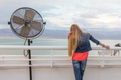 Молодая женщина Blondie представляя вид на море вентилятора балкона Стоковое Изображение