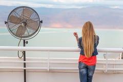 Молодая женщина Blondie представляя вид на море вентилятора балкона Стоковая Фотография