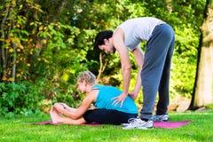 Молодая женщина outdoors делая йогу с тренером Стоковые Фотографии RF
