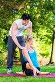 Молодая женщина outdoors делая йогу с тренером Стоковые Изображения RF