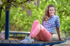 Молодая женщина outdoors против предпосылки цветя глицинии Стоковое Изображение RF