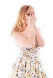 Молодая женщина peeking через руки покрывая сторону Стоковое Изображение