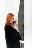 Молодая женщина redhead с кружкой черного кофе стоковая фотография