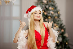 Молодая женщина santa красоты около рождественской елки Модный lu Стоковое фото RF