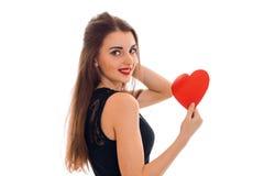 Молодая жизнерадостная дама брюнет с красным сердцем в руках усмехаясь на камере изолированной на белой предпосылке красный цвет  Стоковая Фотография