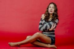 Молодая жизнерадостная девушка в шортах джинсовой ткани и striped свитер идя в моложавый стиль Стоковые Фотографии RF