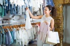 Молодая жизнерадостная женщина выбирая платье младенца стоковое фото