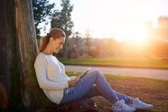 Молодая жизнерадостная женщина наблюдая смешное видео или читая электронную книгу на сенсорной панели пока отдыхающ outdoors, Стоковая Фотография RF