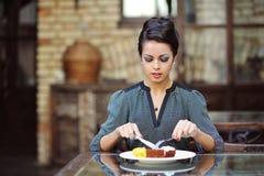 Молодая жизнерадостная женщина на обеде на ресторане Стоковые Изображения