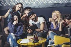 Молодая жизнерадостная компания друзей с чернью, таблеткой и чаем co Стоковые Изображения RF