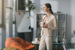 Молодая задумчивая коммерсантка держа чашку и смотря прочь в офисе Стоковая Фотография