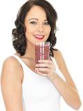 Молодая здоровая женщина держа выпивать стекло смешанного Smoothie ягоды Стоковые Изображения