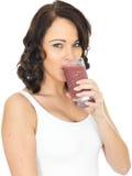 Молодая здоровая счастливая женщина держа выпивать стекло свежего смешанного Smoothie ягод Стоковые Изображения RF