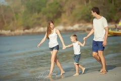 Молодая игра семьи на пляже Стоковое Фото