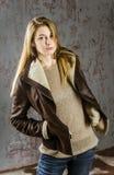 Молодая длинн-с волосами девушка в кожаной куртке с воротником и джинсами меха Стоковые Изображения RF