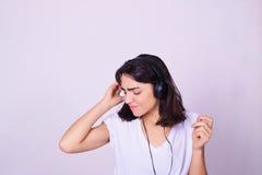 Молодая испанская женщина слушая к музыке с наушниками Стоковая Фотография