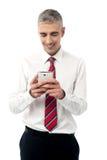 Молодая исполнительная власть используя мобильный телефон стоковое изображение