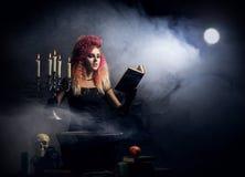 Молодая и красивая ведьма делая колдовство в подземелье Стоковые Изображения RF