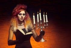 Молодая и красивая ведьма делая колдовство Стоковые Изображения RF