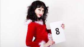 Молодая и красивая женщина в красном пальто держит лист бумаги с номерами Окончательный комплекс предпусковых операций видеоматериал