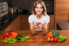 Молодая и красивая женщина домохозяйки варя в кухне стоковые фото