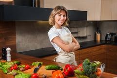 Молодая и красивая женщина домохозяйки варя в кухне Стоковое Фото