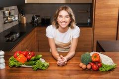 Молодая и красивая женщина домохозяйки варя в кухне стоковые изображения rf
