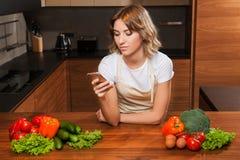 Молодая и красивая женщина домохозяйки варя в кухне стоковое фото rf