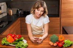 Молодая и красивая женщина домохозяйки варя в кухне стоковая фотография