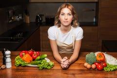 Молодая и красивая женщина домохозяйки варя в кухне Стоковые Изображения