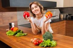 Молодая и красивая женщина домохозяйки держа paprica в ее руках стоковые фото