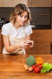 Молодая и красивая женщина домохозяйки делая изображение на ее cellph стоковая фотография