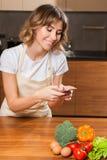 Молодая и красивая женщина домохозяйки делая изображение на ее cellph стоковые изображения rf