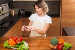 Молодая и красивая женщина домохозяйки делая изображение на ее cellph стоковое фото rf