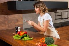 Молодая и красивая женщина домохозяйки делая изображение на ее cellph стоковые фото