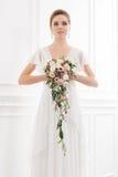 Молодая и красивая невеста при букет представляя в ретро интерьере Стоковые Фото