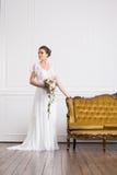 Молодая и красивая невеста при букет представляя в ретро интерьере Стоковое Изображение