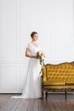 Молодая и красивая невеста при букет представляя в ретро интерьере Стоковая Фотография