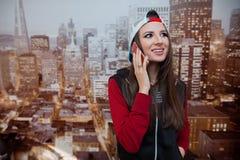Молодая и положительная девушка говорит на телефоне в ее комнате против фона города показанного на обоях Стоковые Фотографии RF