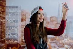 Молодая и положительная девушка сфотографирована на ее smartphone в ее комнате на предпосылке города показанного на Стоковое Фото