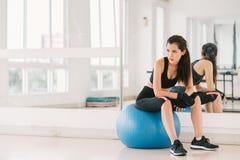 Молодая и решительно сексуальная азиатская девушка на шарике фитнеса на спортзале с космосом экземпляра, спортом и здоровой конце Стоковые Изображения RF