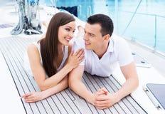 Молодая и счастливая пара ослабляя на шлюпке Стоковые Фото