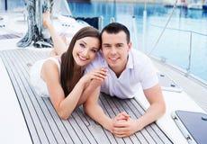 Молодая и счастливая пара ослабляя на шлюпке Стоковые Фотографии RF