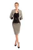 Молодая и элегантная бизнес-леди стоя на белой предпосылке Стоковая Фотография