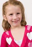 Маленькая девочка в свитере сердца делая смешную сторону Стоковая Фотография RF