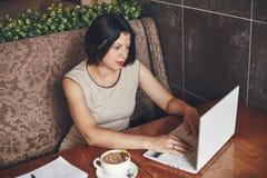 Молодая кавказская коммерсантка с компьтер-книжкой и тетрадью Женщина в кафе Стоковая Фотография RF