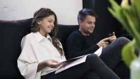 Молодая кассета чтения пар на софе акции видеоматериалы