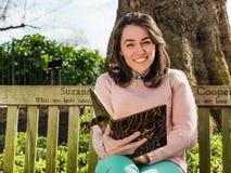 Молодая книга и усмехаться чтения женщины красоты усаженные на скамейку в парке стоковое фото rf